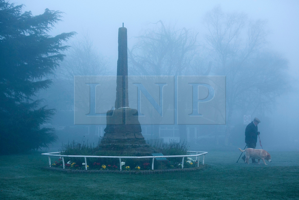 """© Licensed to London News Pictures. 14/03/2014. Meriden, Coventry, UK. Dense fog covered the Midlands earlier today. A man and his dog walk past the """"Centre of England"""" monument in Meriden, near Coventry. Photo credit : Dave Warren/LNP"""