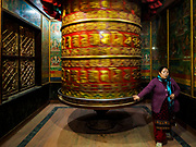 17 MARCH 2017 - KATHMANDU, NEPAL: A woman spins a prayer wheel at a monastery near Boudhanath Stupa in Kathmandu. The stupa is the holiest site in Nepali Buddhism. It is also the center of the Tibetan exile community in Kathmandu. The Stupa was badly damaged in the 2015 earthquake but was one of the first buildings renovated.     PHOTO BY JACK KURTZ