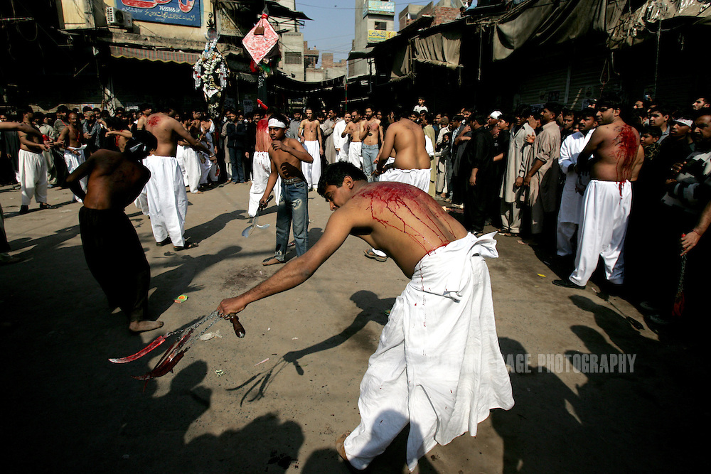 LAHORE, PAKISTAN - FEBRUARY 9: Shia Muslims participate in self-flagelation during Ashura rituals, February 9, 2006, Lahore, Pakistan. Millions of Muslims worldwide observe Ashura during the month of Muharram to mourn the death of the Prophet Mohammed's grandson Immam Hussain. Some Shia participate in self-flagellation to punish themselves for failing to protect the prophet's grandson. Many Shia, however, see this act as unnecessary. During the month of Muharram, many Shia's give generously to the poor and spend time in prayer.  (Photo by Warrick Page)Security is stepped up every year throughout the country during Ashura due to ongoing violence between Shia and Sunni Muslim groups who frequently attack during opposing religious observances.