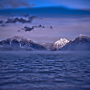 sun sets on snow capped mountains in glacier national park, lake mcdonald