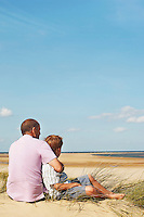 Father and Son sitting on sand dune looking out on Beach back view
