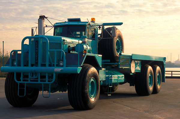 Large flatbed transport truck parked at sunset