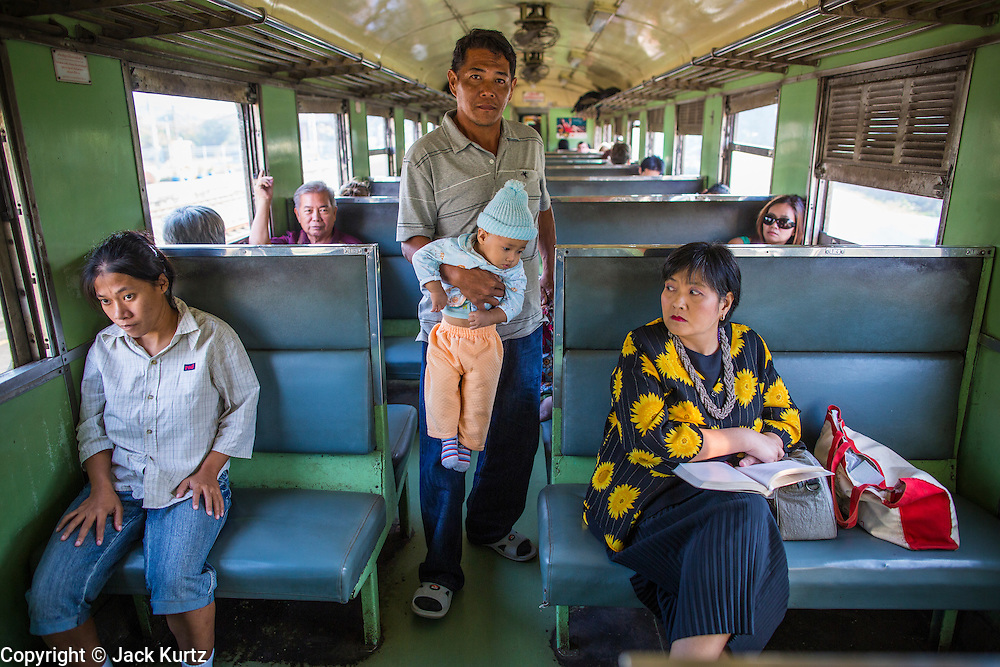 07 JANUARY 2013 - KANCHANABURI, THAILAND:   A man carries his son to their seat in a third class car on the train between Bangkok (Thonburi station) and Kanchanaburi. Thailand has a very advanced rail system and trains reach all parts of the country.    PHOTO BY JACK KURTZ