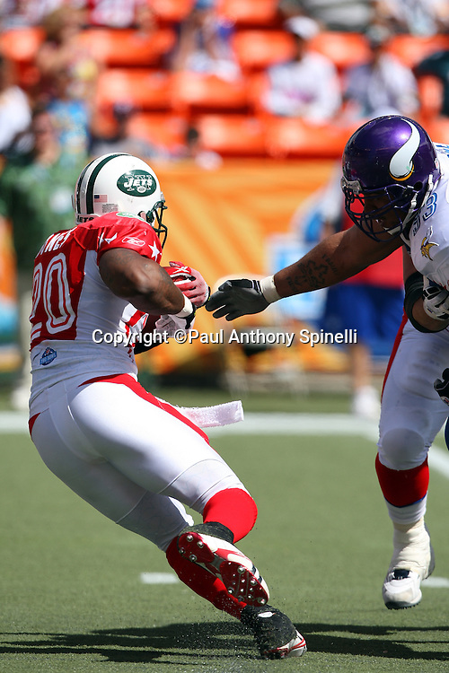 HONOLULU, HI - FEBRUARY 08: AFC All-Stars running back Thomas Jones #20 of the New York Jets runs the ball while trying to avoid the outstretched arm of defensive tackle Kevin Williams #93 of the Minnesota Vikings of the NFC All-Stars in the 2009 NFL Pro Bowl at Aloha Stadium on February 8, 2009 in Honolulu, Hawaii. The NFC defeated the AFC 30-21. ©Paul Anthony Spinelli *** Local Caption *** Thomas Jones;Kevin Williams