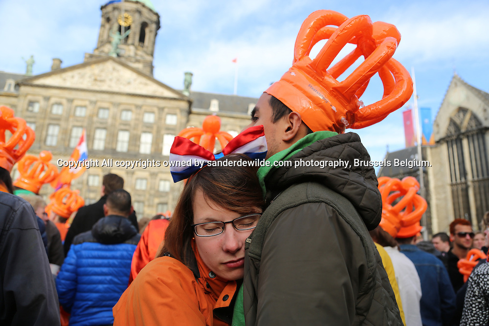 30th April 2013 Amsterdam, Netherlands. Dam Square. Queen Beatrix' abdication takes place, and her son Prince Willem-Alexander will be King of the Netherlands. these people partied all night. The girl sleeps on her boyfriends shoulder, waiting for the action to begin in a few hours