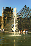 """The Louvre Pyramid """"Pyramide du Louvre"""" is a large glass and metal pyramid surrounded by three smaller pyramids, in the main courtyard or Cour Napoléon, of the Louvre Palace in Paris. The large pyramid serves as the main entrance to the Louvre Museum. and has become one of the landmarks of the city of Paris."""