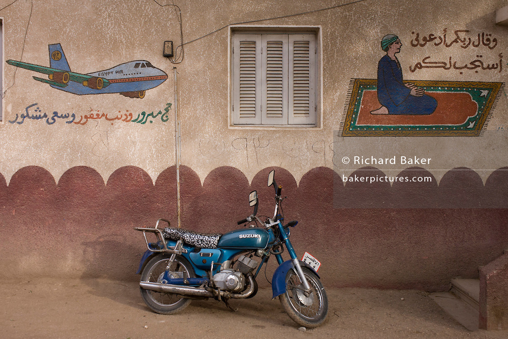A parked motorcycle under Islamic and travel murals in a street of the village of Bairat on the West Bank of Luxor, Nile Valley, Egypt.