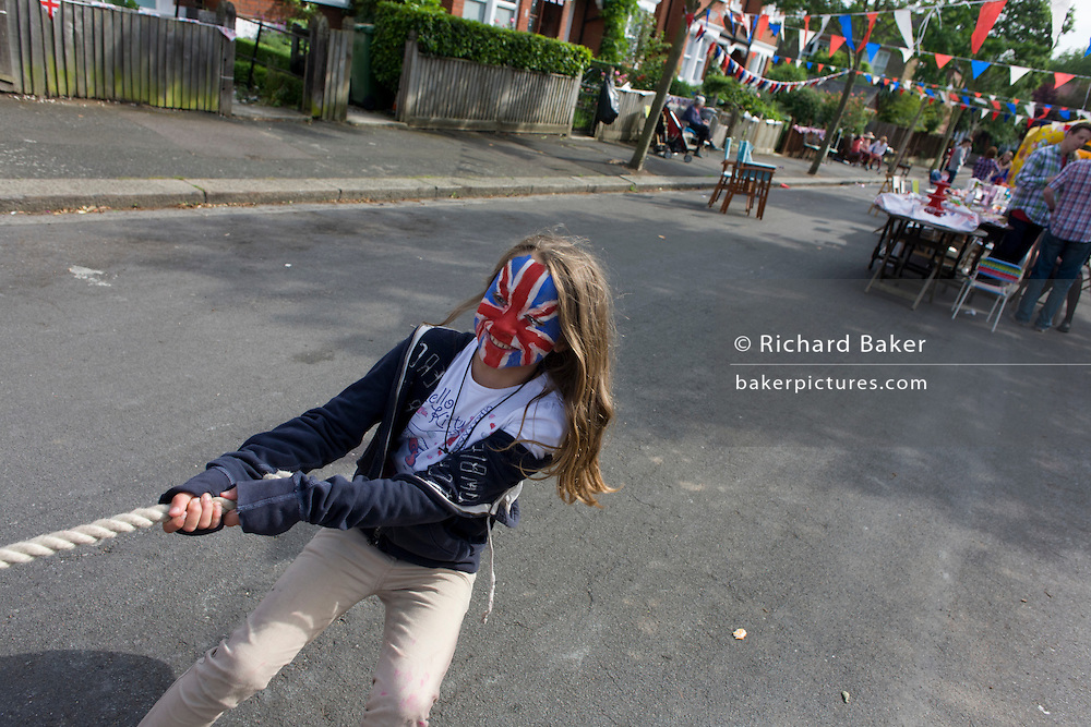 Girl with painted Union Jack face pulls during tug-o-war game at a neighbourhood street party in Dulwich, south London celebrating the Diamond Jubilee of Queen Elizabeth. A few months before the Olympics come to London, a multi-cultural UK is gearing up for a weekend and summer of pomp and patriotic fervour as their monarch celebrates 60 years on the throne and across Britain, flags and Union Jack bunting adorn towns and villages.