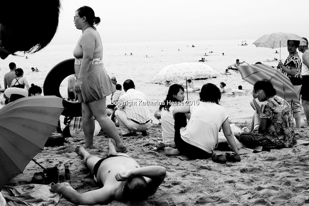 BEIDAIHE, AUG.20-2010 : Chinese tourists enjoy themselves at the beach  in Qingdao. Qingdao is one of China's  most renowned beach resorts  and  draws millions of visitors every year which is little by Chinese standards .