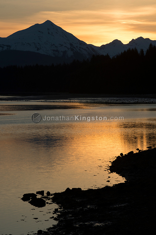Sunset behind snow capped mountains in Bartlett cove, Alaska.