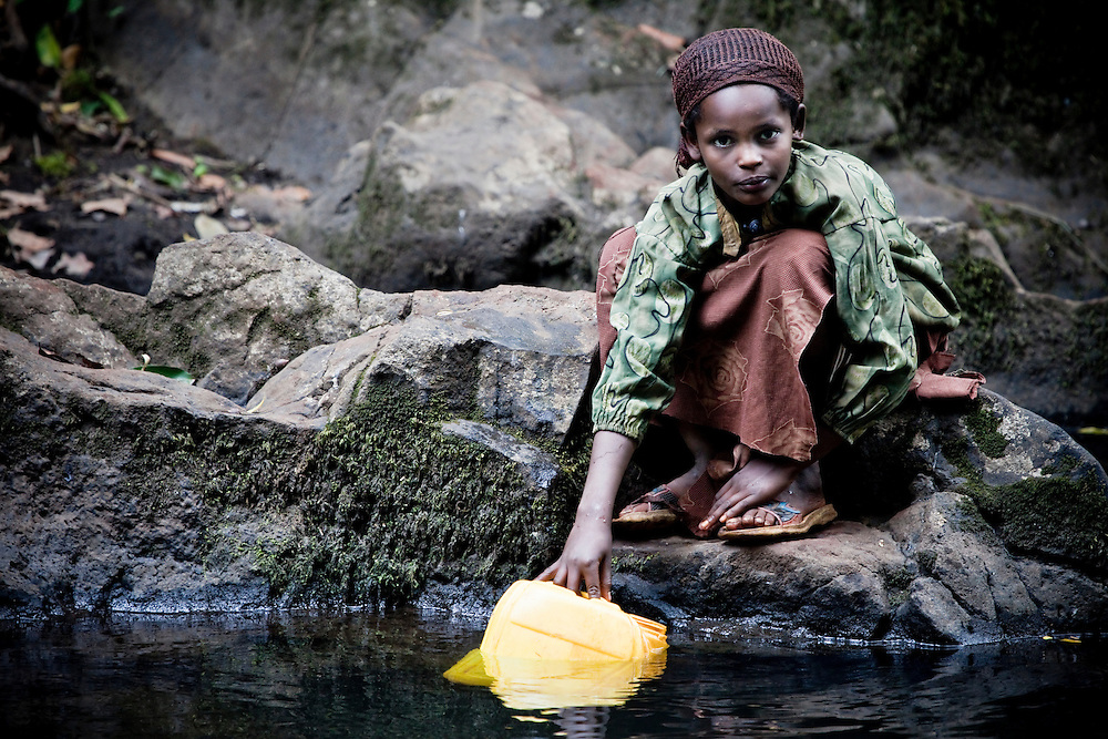 A girl collects water from a stream in the Bale Mountains of Southern Ethiopia