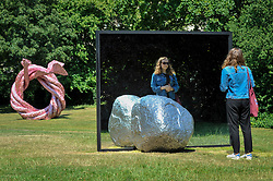 "© Licensed to London News Pictures. 05/07/2017. London, UK. (L to R) ""Fiddlers Fortune"", 2010, by John Chamberlain and ""Big Be-Hide"", 2017, by Alicja Kwade.  The Frieze Sculpture festival opens to the public in Regent's Park.  Featuring outdoor works by leading artists from around the world the sculptures are on display from 5 July to 8 October 2017.  Photo credit : Stephen Chung/LNP"