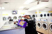 Roberto Barajas pours detergent into a wash at Coin Laundry in East Point, Georgia December 30, 2009. Monica, Roberto's wife, has been separated from her husband and son so she can continue dialysis in Mexico.