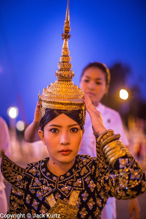 "01 FEBRUARY 2013 - PHNOM PENH, CAMBODIA:  A Cambodian Aspara dancer prepares to walk in the funeral procession of former Cambodian King Norodom Sihanouk. Norodom Sihanouk (31 October 1922 - 15 October 2012) was the King of Cambodia from 1941 to 1955 and again from 1993 to 2004. He was the effective ruler of Cambodia from 1953 to 1970. After his second abdication in 2004, he was given the honorific of ""The King-Father of Cambodia."" Sihanouk died in Beijing, China, where he was receiving medical care, on Oct. 15, 2012. His cremation is will be on Feb. 4, 2013. Over a million people are expected to attend the service.   PHOTO BY JACK KURTZ"