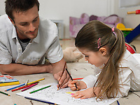 Father and daughter (3-4) colouring in book on floor