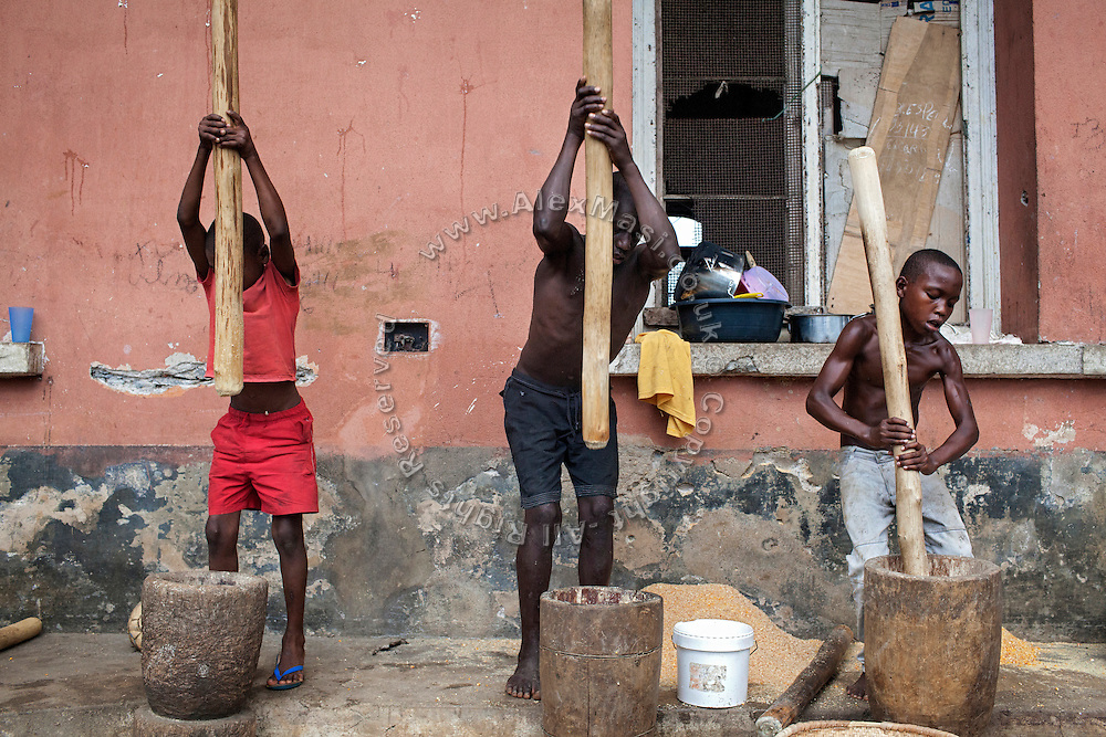 Boys living in the old hospital of Roça Agostinho Neto are producing maize flour to be sold at the local market, on the island of Sao Tome, Sao Tome and Principe, (STP) a former Portuguese colony in the Gulf of Guinea, West Africa.