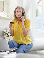 Woman holding credit card using phone in living room