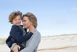 mother holding a little boy outdoors on the beach