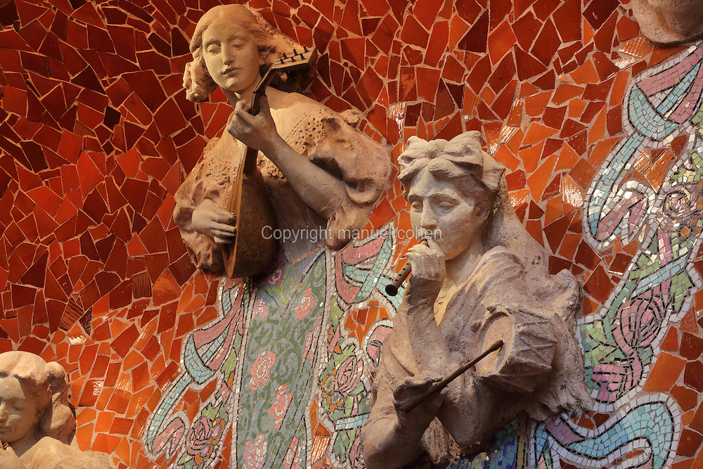 Sculptures of muses playing a lute and a flageolet and a drum, by Eusebi Arnau, with mosaics by Lluis Bru, around the back wall of the stage in the Concert Hall, at the Palau de la Musica Catalana, built 1905-8 and designed by the Catalan Modernist architect Lluis Domenech i Montaner, 1850-1923, in Casc Antic, Barcelona, Catalonia, Spain. The hall seats 2015 people, has a Walcker pipe organ and stepped stage and is illuminated entirely during the day by windows and a huge stained glass drip-shaped skylight by Rigalt Granell & Cia. The hall was built for the Orfeo Catala choral society in Catalan Modernist style, with art nouveau inspired organic forms and much attention to decorative detail. The concert hall was listed in 1997 as a UNESCO World Heritage Site. Picture by Manuel Cohen