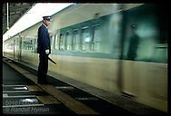 Stationmaster watches blur of bullet train (Shinkansen) as it slows to stop at Utsunomiya. Japan