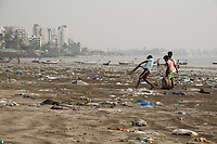 Indian boys play game of cricket among plastic garbage and other pollution at Versova Beach, Mumbai, India