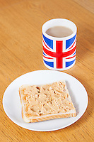 British coffee mug and slice of bread with butter on table