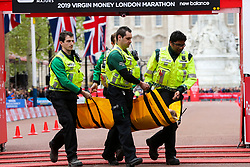 © Licensed to London News Pictures. 28/04/2019. London, UK.  A woman ruuner is helped by the medical staff at the finish line of 2019 Virgin Money London Marathon. Photo credit: Dinendra Haria/LNP