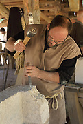 Stone cutter at work carving stone with a hammer and chisel in a workshop at the Chateau de Guedelon, a castle built since 1997 using only medieval materials and processes, photographed in 2017, in Treigny, Yonne, Burgundy, France. The Guedelon project was begun in 1997 by Michel Guyot, owner of the nearby Chateau de Saint-Fargeau, with architect Jacques Moulin. It is an educational and scientific project with the aim of understanding medieval building techniques and the chateau should be completed in the 2020s. Picture by Manuel Cohen