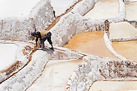 Man working at the salt pans near Maras, Peru.  The pans are fed by a natural spring and the salt has been collected since pre-Inca times.