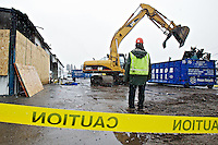 A demolition crew from Cannon Hill Industries separates the metal sheeting from the former store front for Helmet Outlet USA and a Kirby vacuum business Wednesday in Dalton Gardens. The businesses were destroyed in a suspicious fire March 2 which a Kootenai County fire marshall said he believed the fire was an arson.