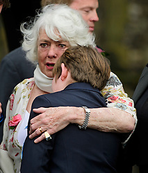 © Licensed to London News Pictures. 18/04/2016. Shirley, UK.  Ronnie Corbett's wife, Anne comforts a young boy following the funeral of comedian, actor, writer Ronnie Corbett at St John the Evangelist Church in Shirley near Croydon. Corbett, who was most famous for his comedy sketch show  The Two Ronnies, performed with the late Ronnie Barker, died at the age of 85. Photo credit: Ben Cawthra/LNP