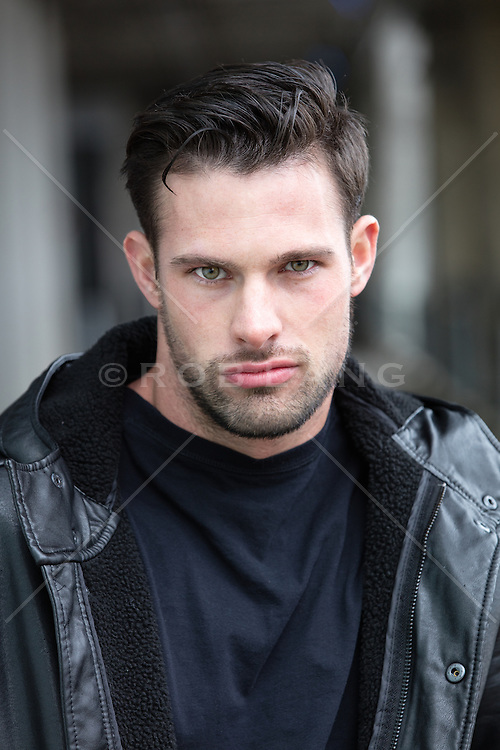 portrait of a rugged man with green eyes and dark hair