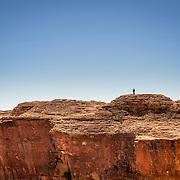 Lone hiker on top of red rock wall at Kings Canyon