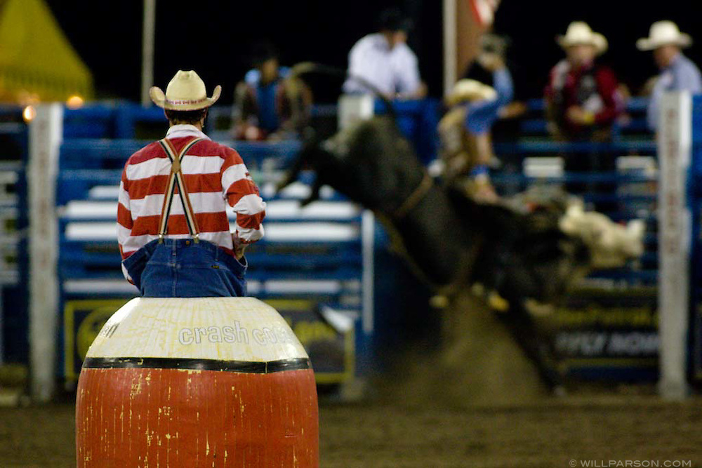 Canadian rodeo clown Crash Cooper looks on as bullrider Renato Nunes takes a spin on Alley Cat during the PBR rodeo at the Del Mar Fairgrounds in Del Mar, California on July 27th, 2008.  It was the second night of the PBR's tour stop in Del Mar.