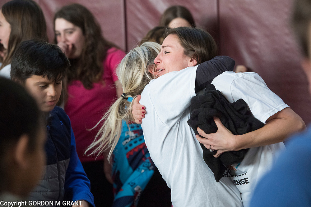 Cara Nelson, right, a 7th grade social studies teacher at the East Hampton Middle School, gets a hug from fellow teacher Lea Bryant, during a sendoff in her honor, at the school in East Hampton, Jan. 18, 2018. Nelson will leave next week to participate in a trip where she will run seven marathons in seven days on seven continents.