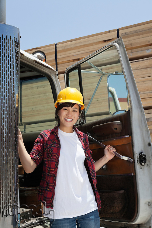 Portrait of an Asian female industrial worker standing by vehicle door