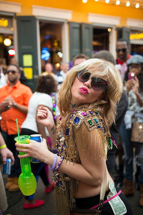 A young woman holding alcoholic beverages is among the revelers on Bourbon Street during Mardi Gras weekened, two days away from Fat Tuesday.