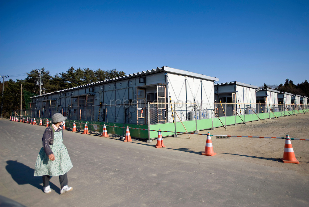 An elderly woman walks past prefab housing set up to accommodate 36 families who lost their homes during the March 11 magnitude 9 quake and subsequent tsunami in Rikuzentakata on April 5, 2011..Photographer: Robert Gilhooly