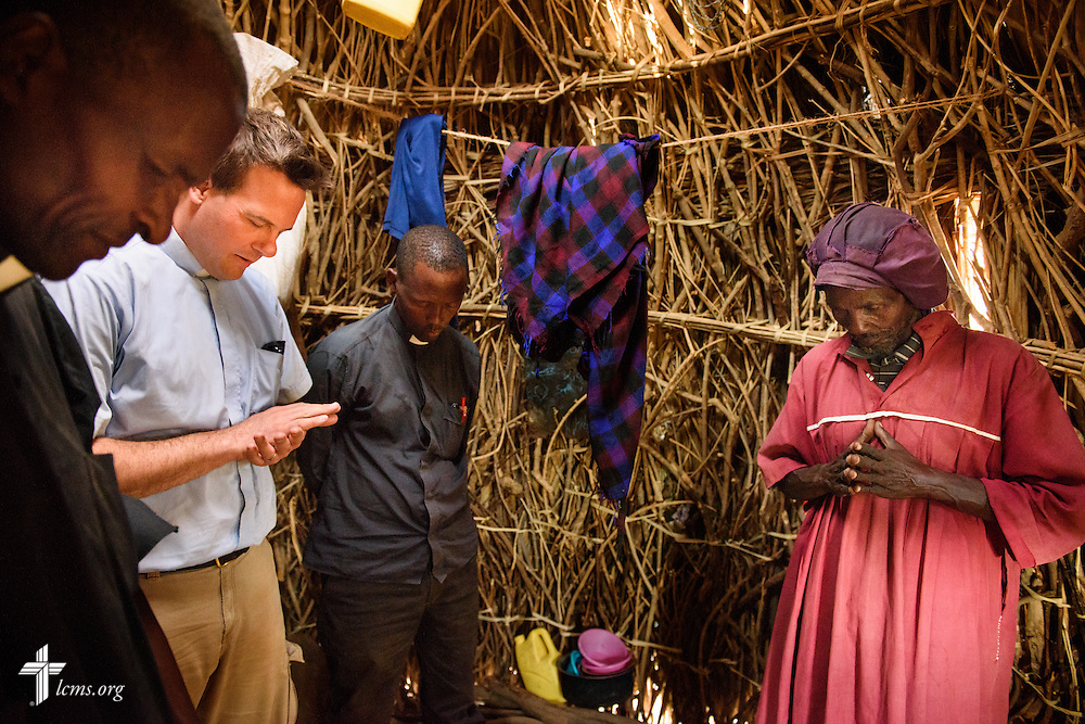 The Rev. Shauen Trump, LCMS missionary and area director for Eastern and Southern Africa, prays with a man in his small village located in the Turkana region of northwest Kenya on Friday, Oct. 16, 2015. Trump is flanked by the Rev. Daniel Mutai (left), pastor in the Evangelical Lutheran Church in Kenya (ELCK) and the Rev. Benjamin Lemosi, general secretary of the ELCK. LCMS Communications/Erik M. Lunsford