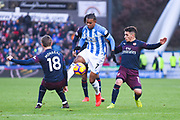 Juninho Bacuna of Huddersfield Town (7) nips past Nacho Monreal of Arsenal (18) and Lucas Torreira of Arsenal (11) during the Premier League match between Huddersfield Town and Arsenal at the John Smiths Stadium, Huddersfield, England on 9 February 2019.