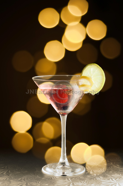 Cocktail drink in a martini glass set against warm, sparkling, golden lights.