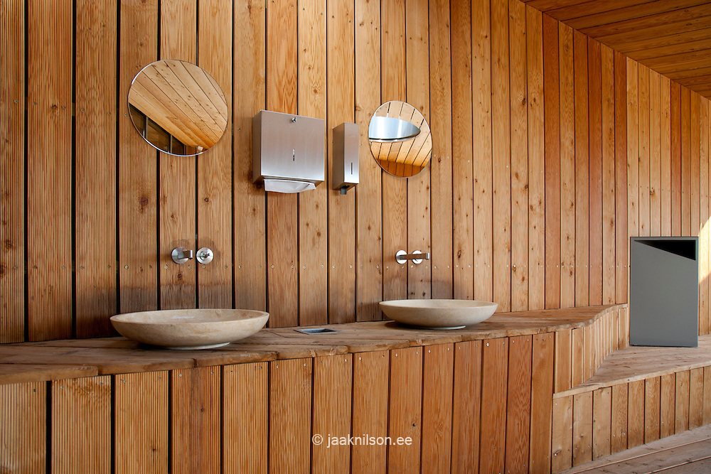 Restrooms, sink and mirrors. Rest area with wooden floor and paneling in Estonian Road Museum