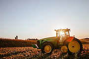Farmer driving a tractor on the field. <br /> Photographed by editorial lifestyle Texas photographer Nathan Lindstrom