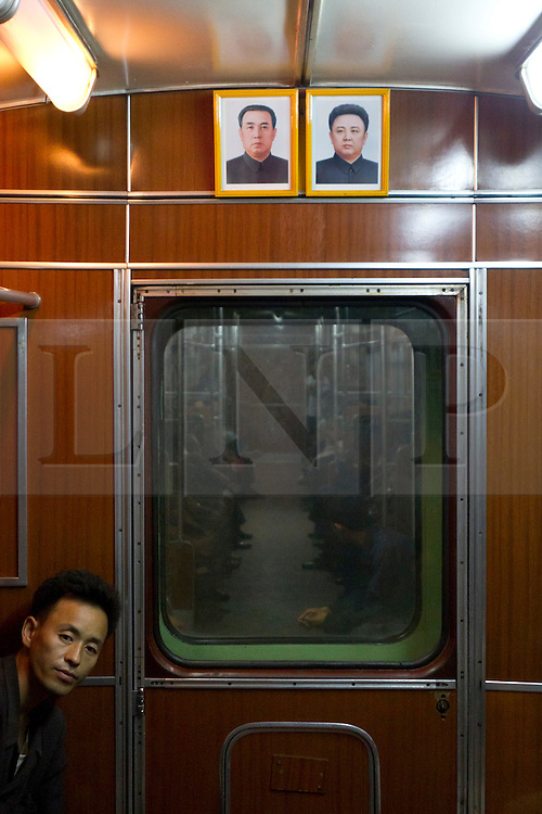 © Licensed to London News Pictures. 10/08/2011. Pyongyang, North Korea. A Pyongyang citizen looks down a train carriage which carries a portrait of the country's leader, Kim Jong-il and his father Kim Il Sung.  The Pyongyang metro is one of the deepest in the world, buried at around 100m below the city surface, every station doubles as a bomb shelter for citizens.  Photo credit : James Gourley/LNP/