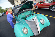 LANGHORNE, PA - JULY 06:  Shirley Rooney and her husband Ed Rooney (behind her) of Philadelphia, Pennsylvania peak into an automobile during a classic car show at the Blue Fountain Diner that also included music, drawings and other entertainment July 6, 2014 in Langhorne, Pennsylvania. Among the car clubs participating were the Philadelphia Modifiers, Street Rod Clubs, Latin Cruisers and Old Frogs.  (Photo by William Thomas Cain/Cain Images)
