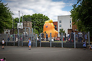 School children play basketball as the Trump Baby sitting team give the six metre high inflatable TrumpBaby his second London outing in Bingfield Park, Kings Cross , London, United Kingdom. 10th July 2018. He WILL fly above Parliament Square in Westminster when the real Trump, president of the United States arrives in the United Kingdom on the 13th of July 2018.  (photo by Andy Aitchison / Trumpbaby Sitter)