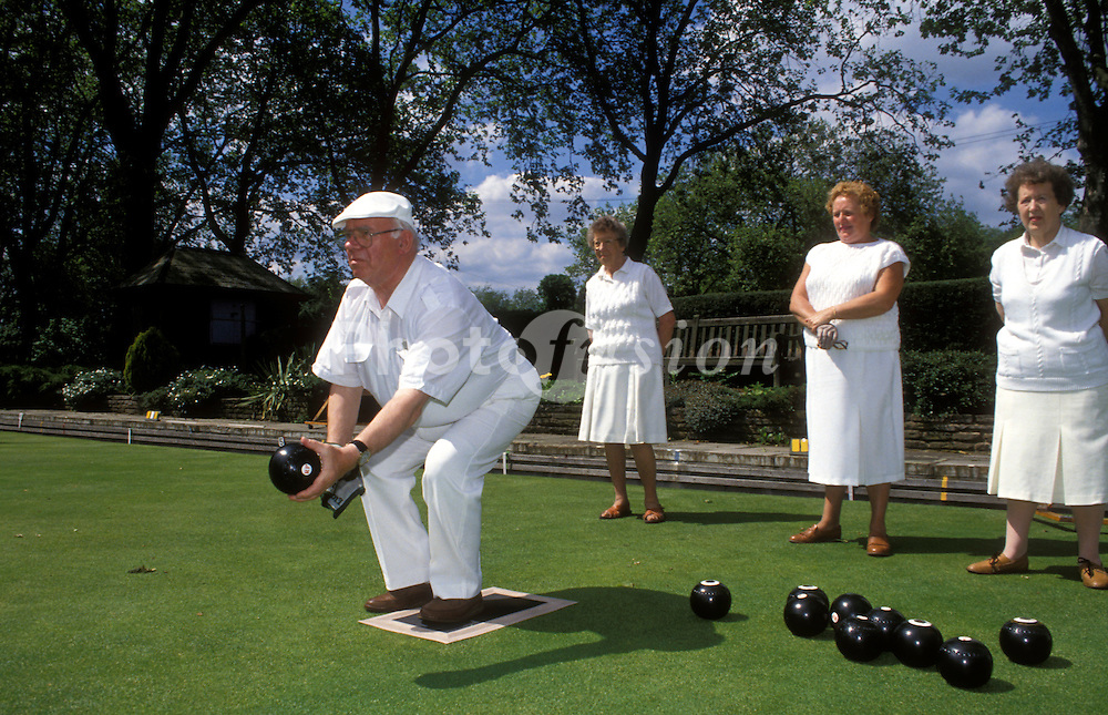 Elderly men & women bowling in the park UK