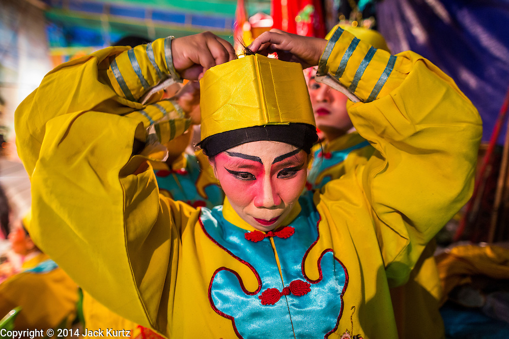 "25 JANUARY 2014 - BANG LUANG, NAKHON PATHOM, THAILAND: Performers get into character for a Chinese opera performance in a small town near Bang Luang, Nakhon Pathom, Thailand. Chinese opera was once very popular in Thailand, where it is called ""Ngiew."" It is usually performed in the Teochew language. Millions of Chinese emigrated to Thailand (then Siam) in the 18th and 19th centuries and brought their cultural practices with them. Recently the popularity of ngiew has faded as people turn to performances of opera on DVD or movies. There are still as many 30 Chinese opera troupes left in Bangkok and its environs. They are especially busy during Chinese New Year when travel from Chinese temple to Chinese temple performing on stages they put up in streets near the temple, sometimes sleeping on hammocks they sling under their stage.     PHOTO BY JACK KURTZ"