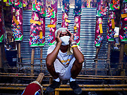 "20 OCTOBER 2017 - BANGKOK, THAILAND: A volunteer waits to help devotees at Chao Zhou Shi Kong Shrine in Bangkok's Chinatown on the first day of the ""Vegetarian Festival"", what Thais call the Taoist Nine Emperor Gods Festival, in the Chinatown neighborhood of Bangkok, Thailand. It is a nine-day Taoist celebration beginning on the eve of 9th lunar month of the Chinese calendar. For nine days people participating in the festival wear only white and don't eat meat, poultry, seafood, and dairy products. The vegetarian festival is celebrated throughout Thailand, but especially in Phuket and Bangkok, cities with large ethnic Chinese communities.       PHOTO BY JACK KURTZ"