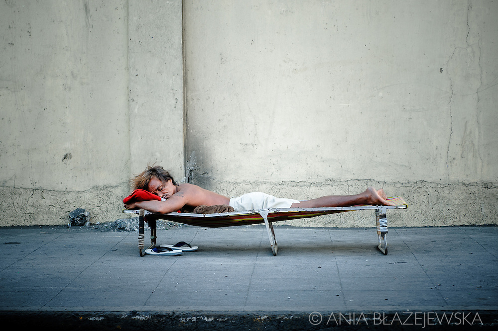 Philippines, Metro Manila. A homeless man sleeping in a bed just at the street of Navotas.